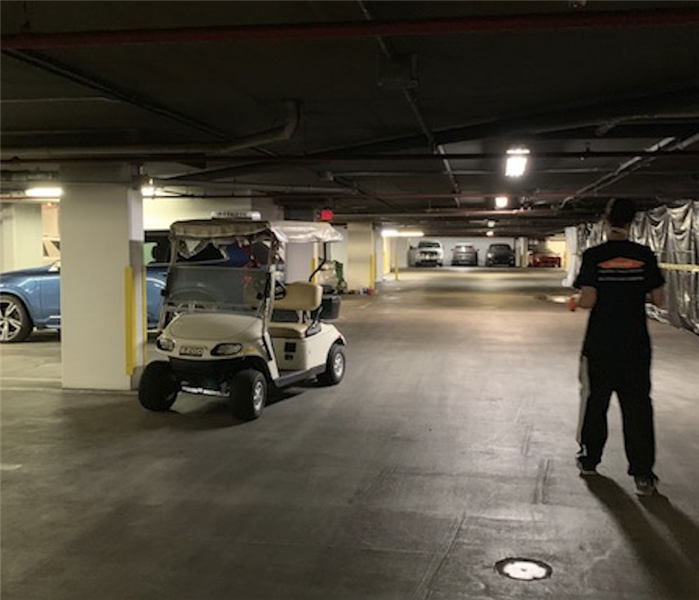 Inside a parking garage with a golf cart parked and a SERVPRO employee standing under the smoke damaged ceiling