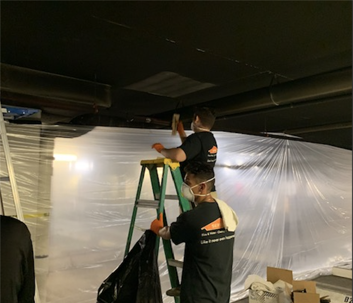 Two SERVPRO employees wearing protective gloves and mask, one on a ladder cleaning smoke damage and other man holding ladder