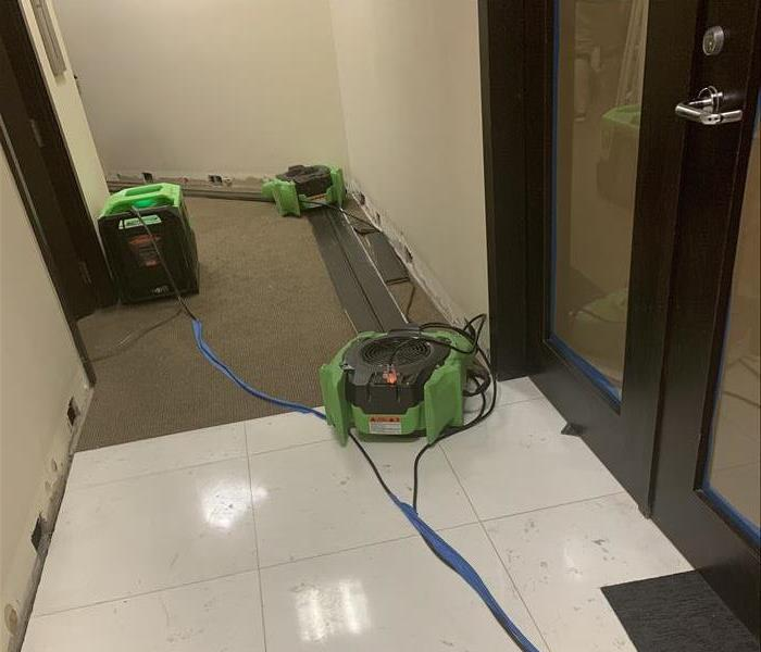 Office hallway with cream walls and dark carpets containing green air movers strategically placed for drying