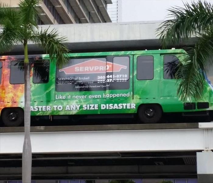 Metro mover car with SERVPRO of Brickell Wrap tall building in background flanked by palm trees