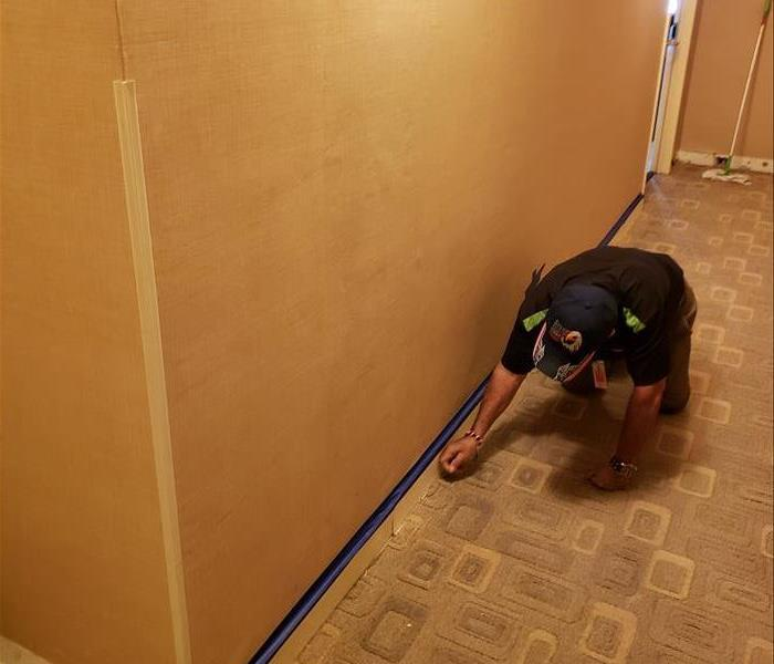 Man on knees cutting out damaged sheetrock in hallway