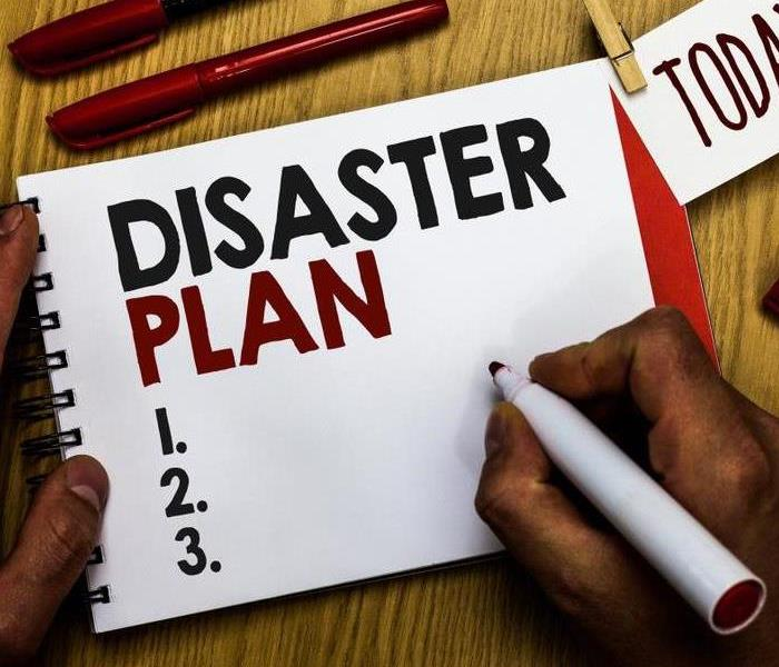 Hand holding a marker with notebook that says Disaster Plan.