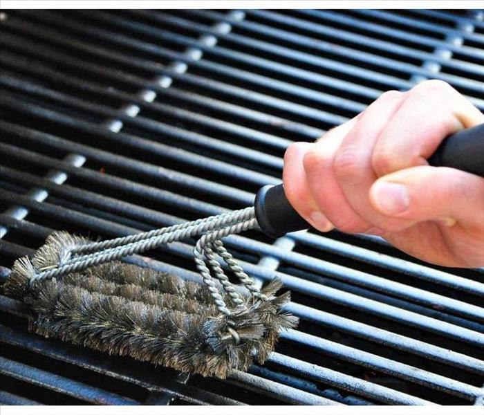 The hand of someone cleaning a barbecue grill