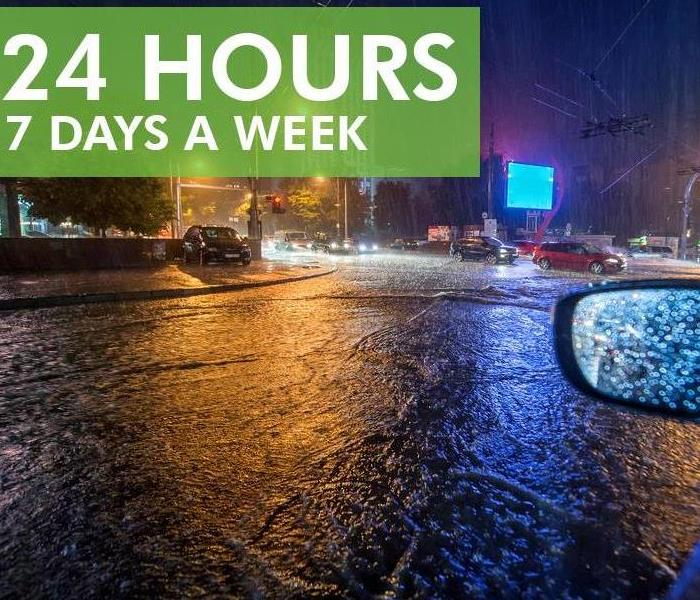 Car driving on flooded streets at night. Text that says 24 hours 7 days a week.