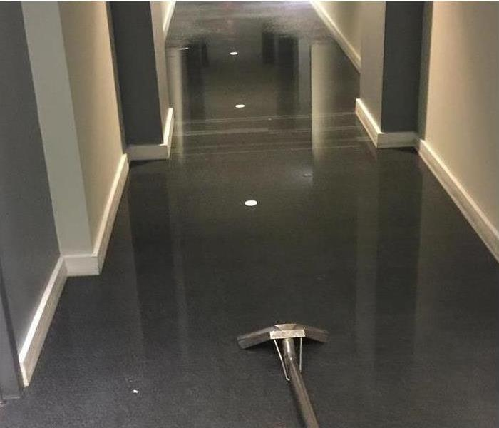 There is a hallway and the floor is covered with water