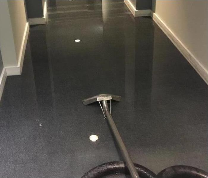 Vaccum laying on the floor of a flooded hallway